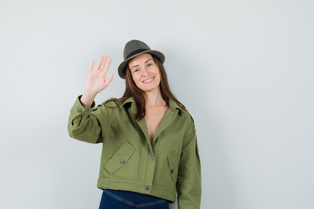 Jeune femme au chapeau de pantalon de veste en agitant la main pour dire au revoir et à la joie