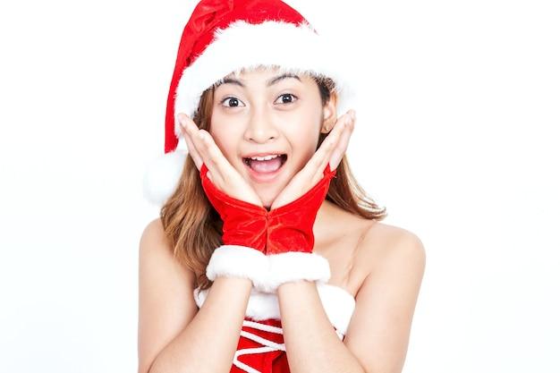 Jeune femme au chapeau de père noël surpris et bouche ouverte sur fond blanc