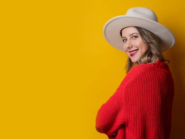 Jeune femme au chapeau et pull rouge