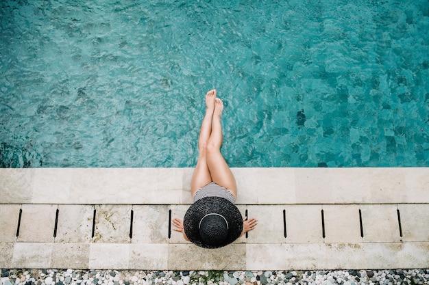 Jeune femme au chapeau relaxant près de la piscine. vue de dessus.