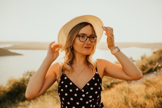 Jeune femme au chapeau en robe à pois se dresse au milieu du pré sur la falaise au-dessus de la mer au coucher du soleil