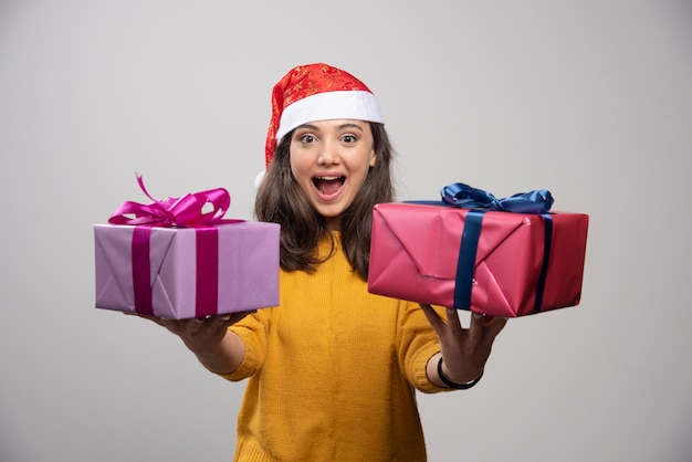 Jeune femme au chapeau rouge du père noël avec des cadeaux de noël.