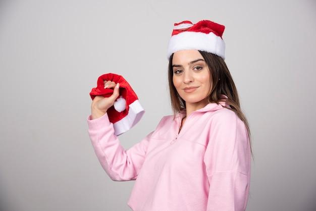 Une jeune femme au chapeau rouge du père noël tenant un chapeau.
