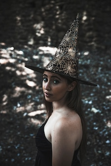 Jeune femme au chapeau de sorcier regardant la caméra