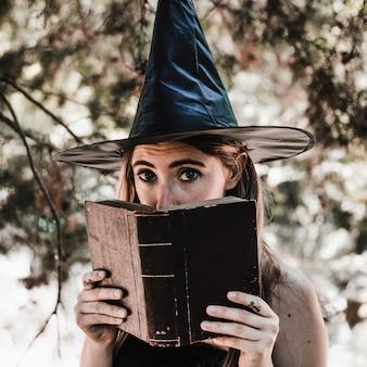 Jeune femme au chapeau de sorcière fermant la bouche avec un livre
