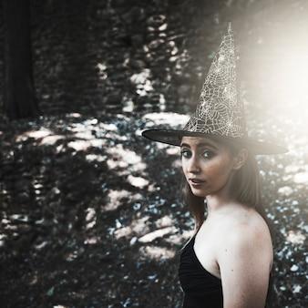 Jeune femme au chapeau de sorcière regardant la caméra en forêt