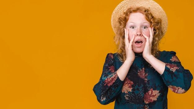 Jeune femme au chapeau touchant les joues et se demandant