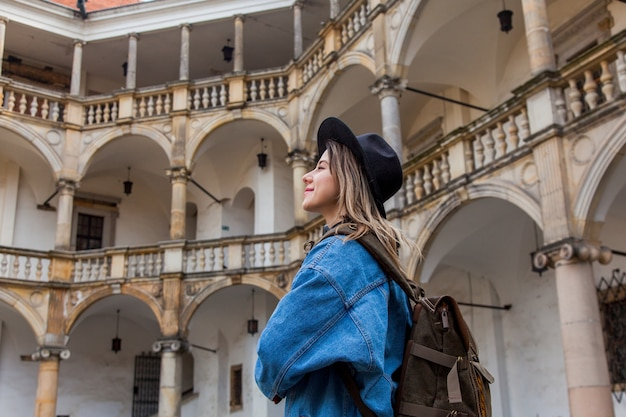 Jeune femme au chapeau et veste en jean avec sac à dos dans le vieux château