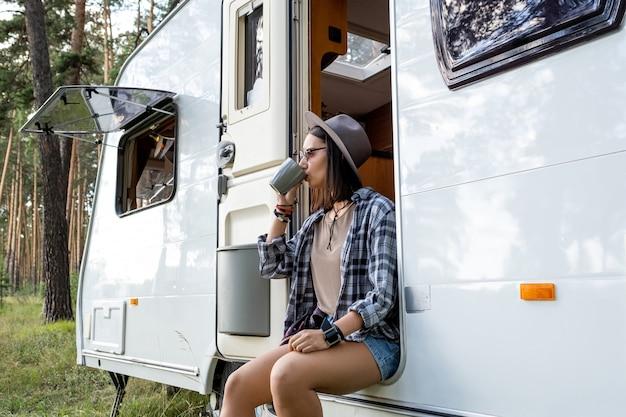 Jeune femme au chapeau et vêtements décontractés buvant du thé tout en se relaxant dans une maison sur roues en randonnée