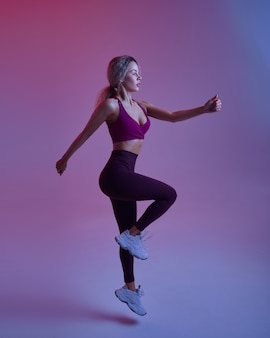 Jeune femme au corps mince pose en studio, fond néon