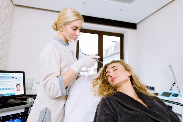 Jeune femme au cours de la procédure d'hydratation professionnelle sur le visage dans le bureau de cosmétologie. cosmétologue femme professionnelle détient splutter pour la procédure d'hydratation pulvérisation d'eau