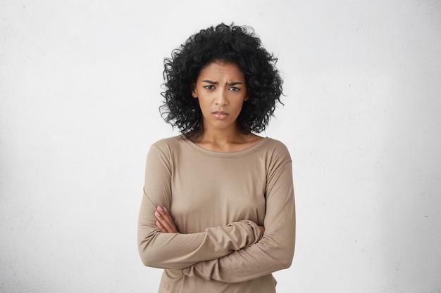 Jeune femme au foyer agacée en colère gardant les bras croisés