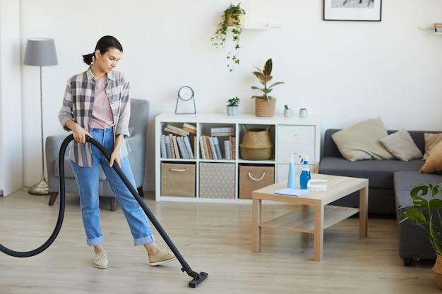 Jeune femme au foyer aspirant le sol dans le salon à la maison, elle fait les travaux ménagers