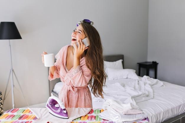 Jeune femme au foyer aux cheveux longs en peignoir rose avec bigoudi sur la tête à la maison au repassage des vêtements. elle parle au téléphone, riant les yeux fermés.
