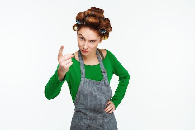 Jeune femme au foyer aux cheveux rouges blâme et gronde à la recherche