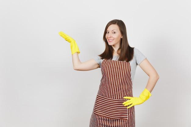 Jeune femme au foyer brune souriante séduisante en tablier rayé, gants jaunes isolés. belle femme de ménage pointant la main de côté