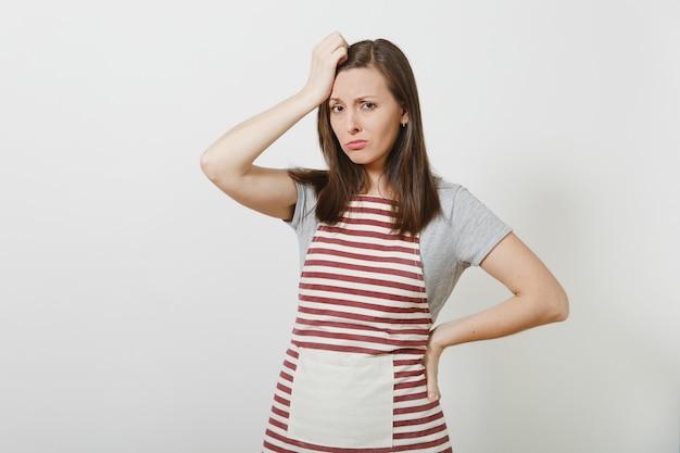 Jeune femme au foyer caucasienne brune fatiguée triste et triste en tablier rayé isolé. belle femme de ménage met et touche sa main à la tête