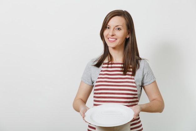 Jeune femme au foyer caucasienne brune souriante séduisante en tablier rayé, t-shirt gris isolé. belle femme de ménage tenant une assiette vide blanche
