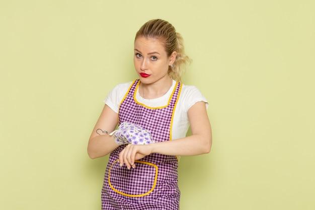 Jeune femme au foyer en chemise et cape colorée tenant des gants de cuisinier soulignant dans son poignet sur vert