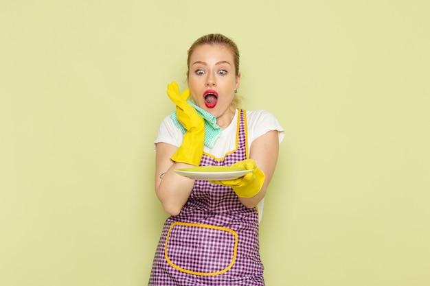 Jeune femme au foyer en chemise et cape de couleur asséchant la plaque sur le vert
