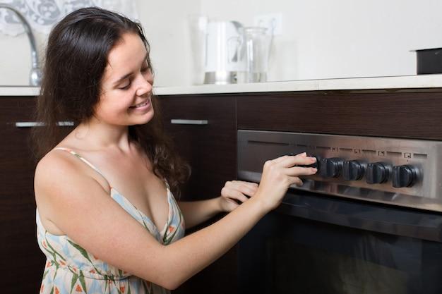 Jeune femme au foyer cuisine au four