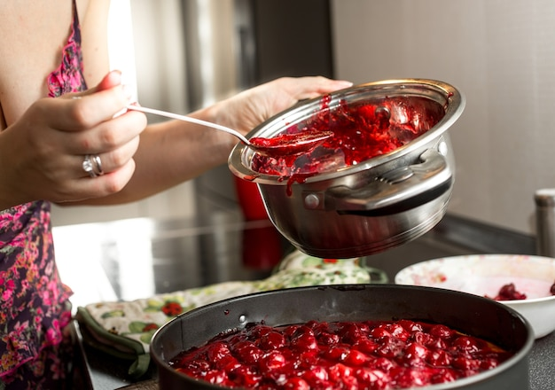 Jeune femme au foyer faisant de la confiture de cerises dans une casserole en métal