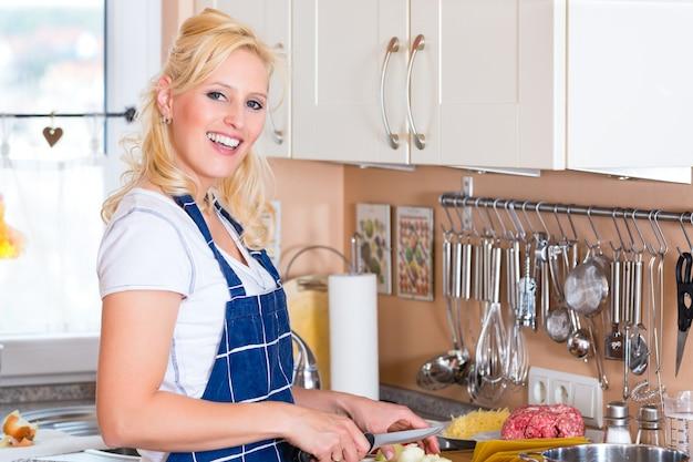 Jeune femme au foyer fait cuire et hacher des oignons