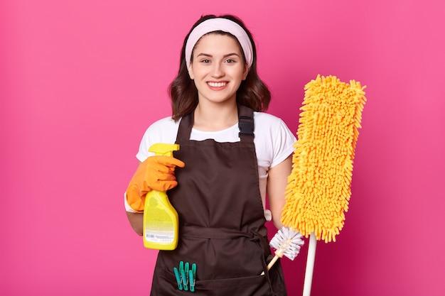 Une jeune femme au foyer joyeuse porte un t-shirt blanc, un tablier marron avec des pinces à linge vertes, des gants en caoutchouc orange pour la protection des mains.