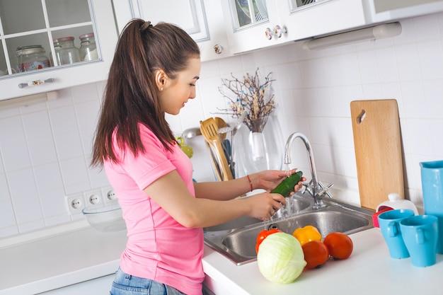 Jeune femme au foyer, laver les légumes frais
