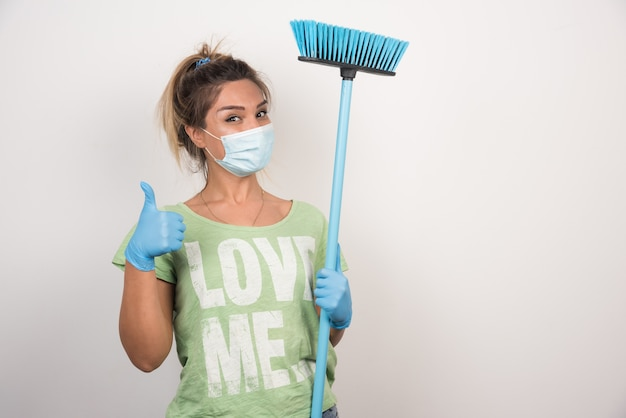 Jeune femme au foyer avec masque et balai faisant signe de pouce en l'air sur le mur blanc.