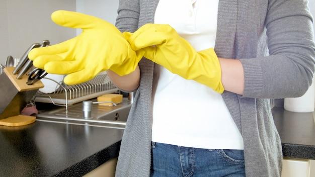 Jeune femme au foyer mettant un gant de protection en caoutchouc jaune avant de faire des travaux ménagers.