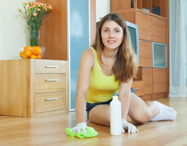 Jeune femme au foyer polissant le parquet