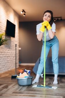 Une jeune femme au foyer a pris une pause de nettoyage et de rêve