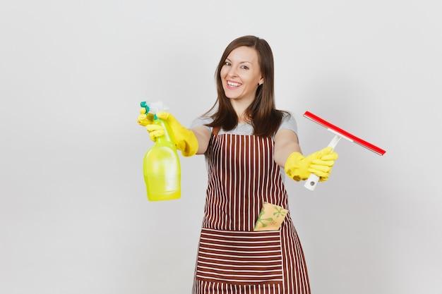 Jeune femme au foyer souriante en gants jaunes, tablier rayé, chiffon de nettoyage en poche isolé