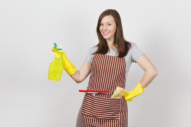 Jeune femme au foyer souriante en gants jaunes, tablier rayé, chiffon de nettoyage, raclette en poche isolée