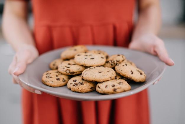 Jeune femme au foyer tient une assiette de biscuits, qu'elle a elle-même préparée