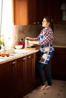 Jeune femme au foyer travaillant sur une cuisine en bois classique avec une grande fenêtre
