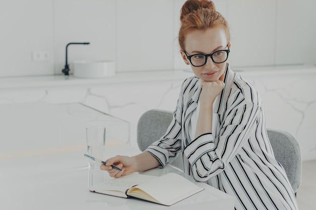 Jeune femme au gingembre concentré pensant au nouveau jour tout en prenant des notes dans un cahier à la cuisine