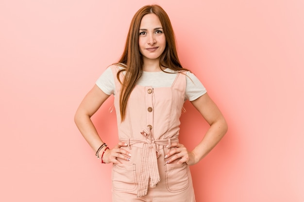 Jeune femme au gingembre avec des taches de rousseur confiant en gardant les mains sur les hanches