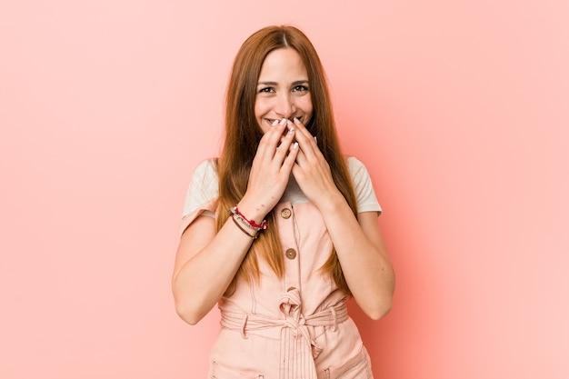 Jeune femme au gingembre avec des taches de rousseur riant de quelque chose, coning bouche avec les mains.