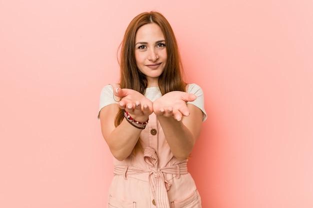 Jeune femme au gingembre avec des taches de rousseur tenant quelque chose avec des paumes, offrant à la caméra.