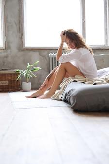 Jeune femme au lit au matin