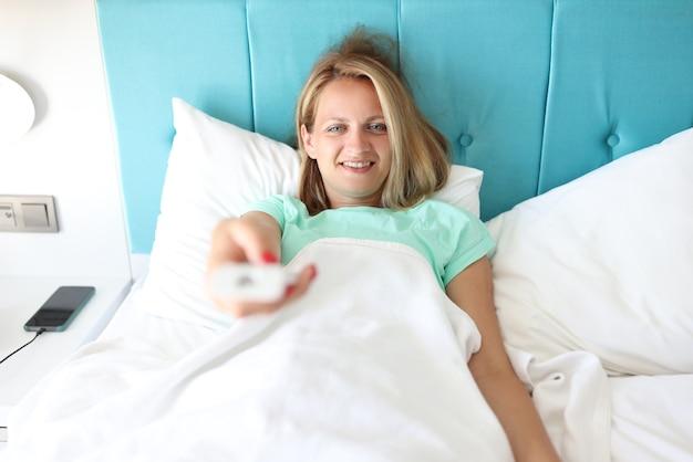 Jeune femme au lit de la chambre d'hôtel tient la télécommande en main