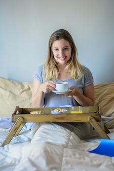 Jeune femme au lit, petit déjeuner