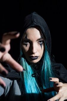 Jeune femme au maquillage effrayant dans la capuche