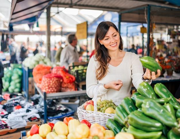 Jeune femme au marché alimentaire local.