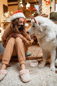 Jeune femme au masque facial célébrant avec un chien les vacances du nouvel an à la maison. concept de quarantaine et d'auto-isolement pendant l'épidémie en vacances