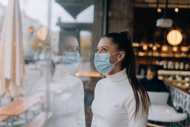 Jeune femme au masque facial debout devant les fenêtres du café