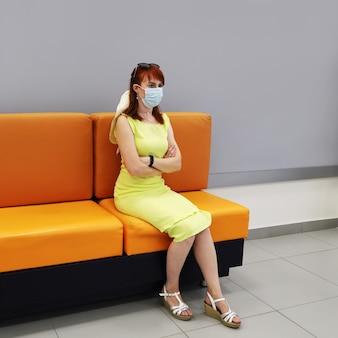 Jeune femme au masque facial médical assise seule dans la salle d'attente