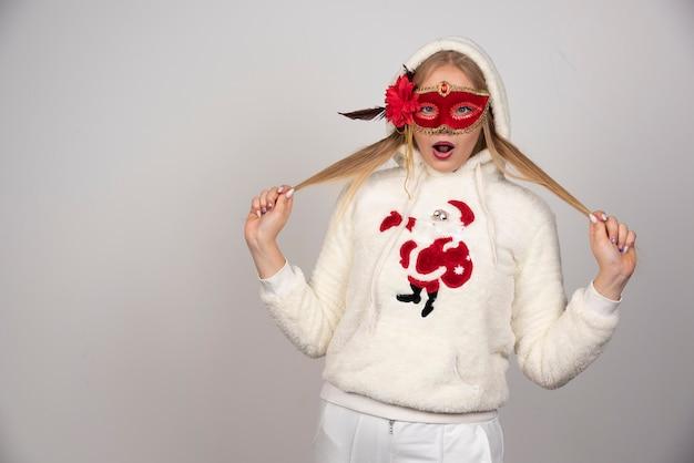 Jeune femme au masque de mascarade faisant une expression surprise.